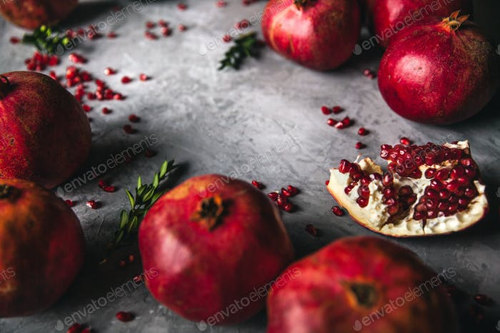Pomegranate fruit. Ripe and juicy pomegranate on rustic grey background