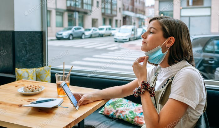 Woman taking off protective mask in a cafe