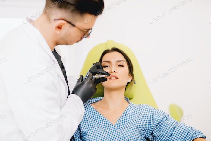 Plastischer Chirurg mit Lippeninjizierbaren für medizinische Verfahren.