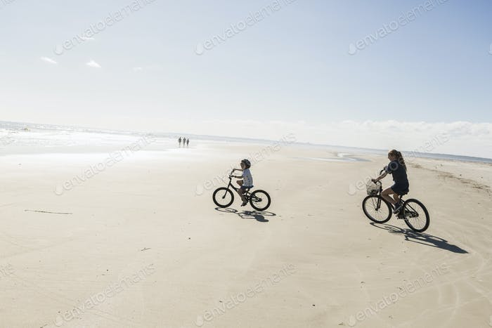 Two children cycling on an open beach, a boy and girl.