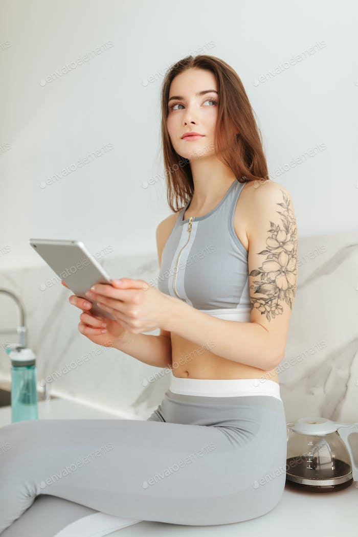 Young lady in sporty top and leggings sitting on the kitchen with laptop thoughtfully looking aside