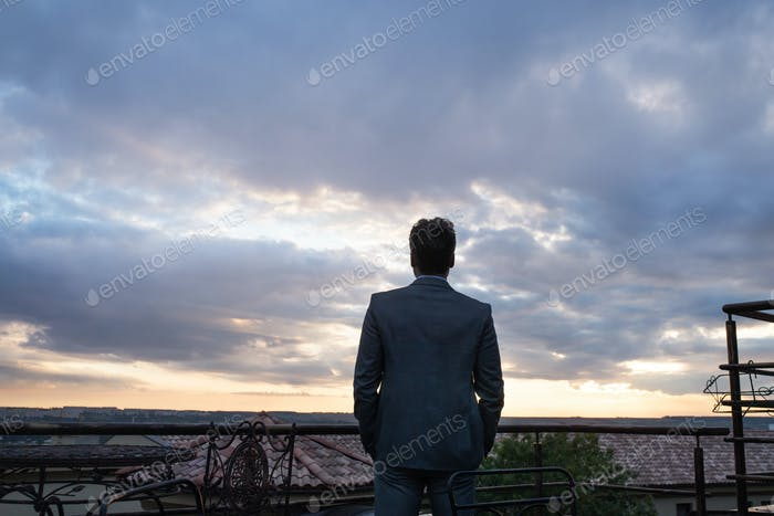 Mature businessman standing in a hotel balcony.
