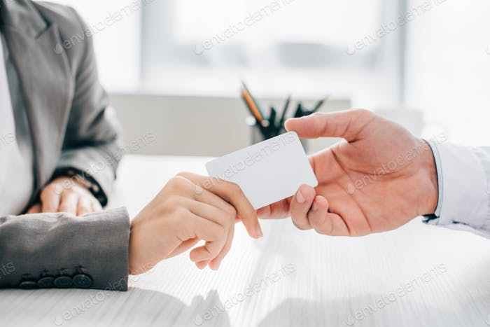 cropped image of patient giving id card to doctor in clinic