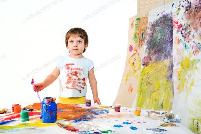 Kleines Mädchen hält Pinsel in den Händen und zieht