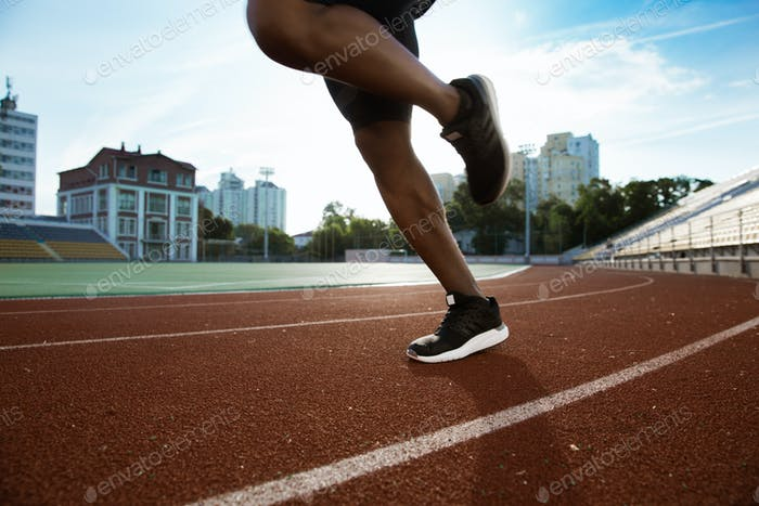 Cropped image of sportsman's legs running