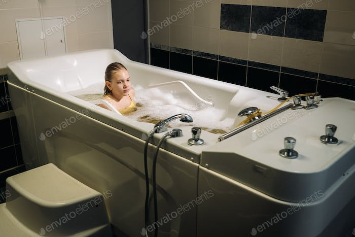 a little girl takes the procedure in a mineral bath. The patient receives water treatments with a