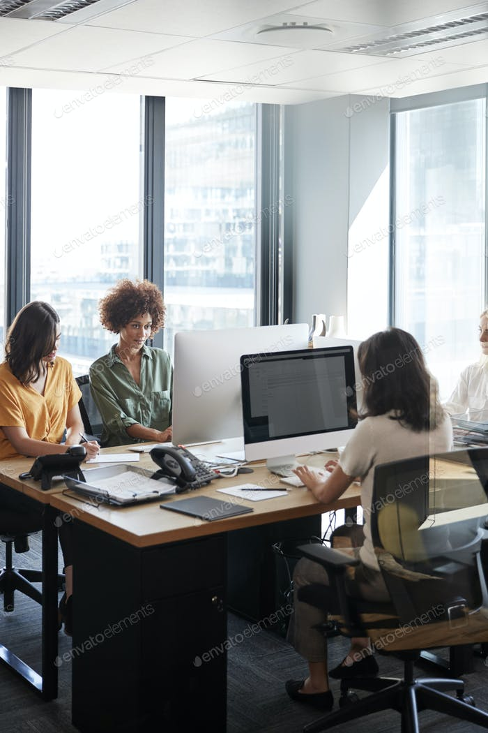 Four female creative colleagues working together in an office, vertical, crop