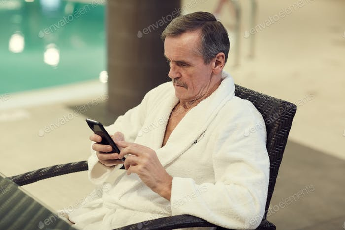 Moderner Senior Man mit Smartphone in SPA