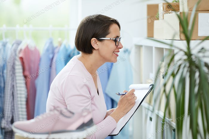 Happy manager of online shop office checking numbers of packed parcels