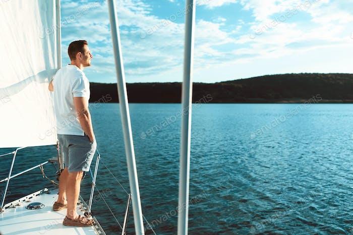 Guy Standing On Yacht Deck Enjoying Sea Breeze Outdoor