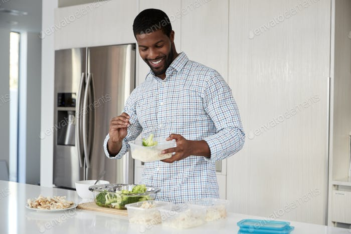 Man In Kitchen Preparing High Protein Meal And Putting Portions Into Plastic Containers