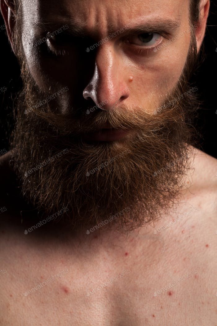 Portrait of tattooed bearded hipster on black background