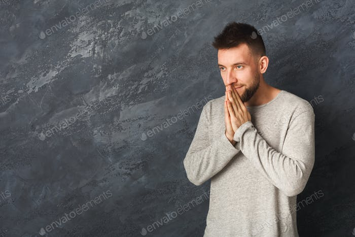 Handsome young man praying on gray background