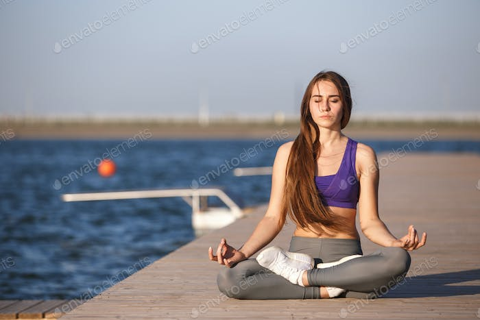 Young beautiful girl with long brown hair in a sports top and tights sits in lotus position on the