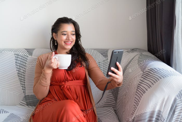 Happy young beautiful Indian woman drinking coffee while taking selfie at home