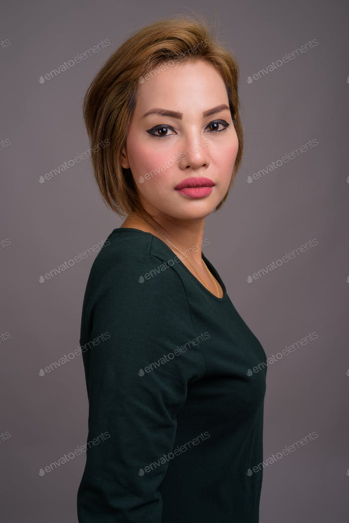 Portrait of beautiful Asian businesswoman against gray background