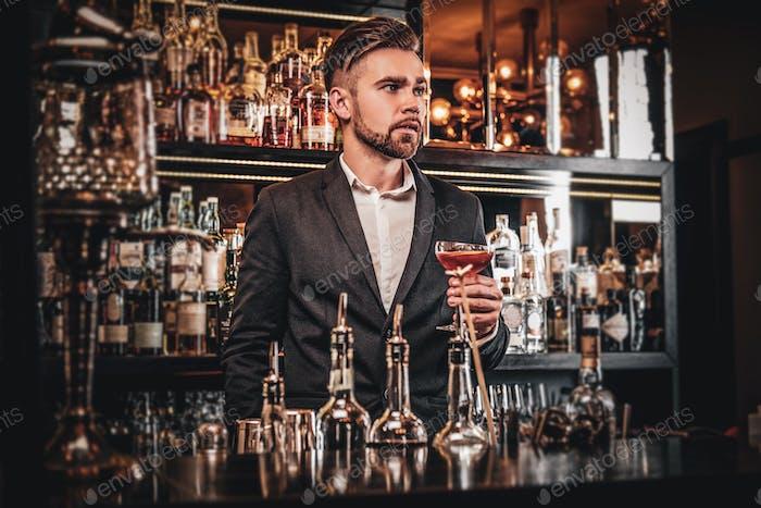 Элегантный ухоженный мужчина пьет алкоголь в баре