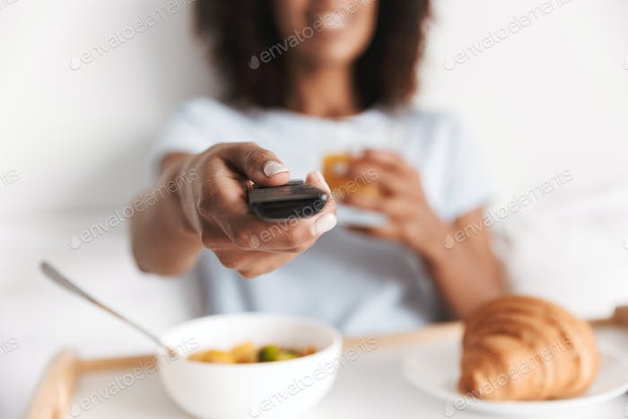 Close up of young african woman holding tv remote