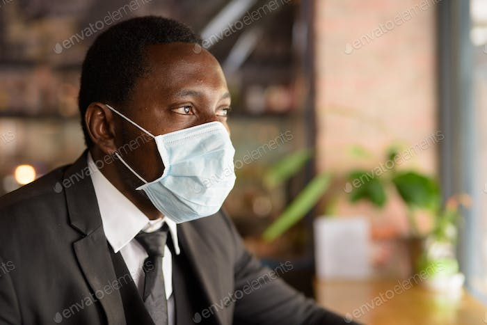 Face of African businessman wearing mask and thinking inside the coffee shop as the new normal