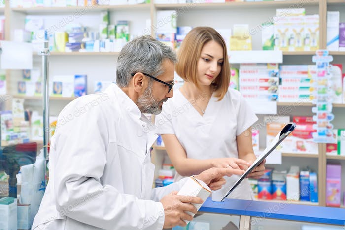 Two pharmacist checking product in folder