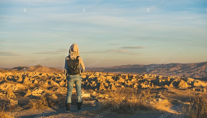 Young woman traveler with backpack watching sunrise, Cappadocia, Central Turkey