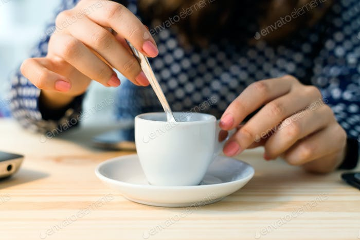 Beautiful young woman drinking coffee in her office.