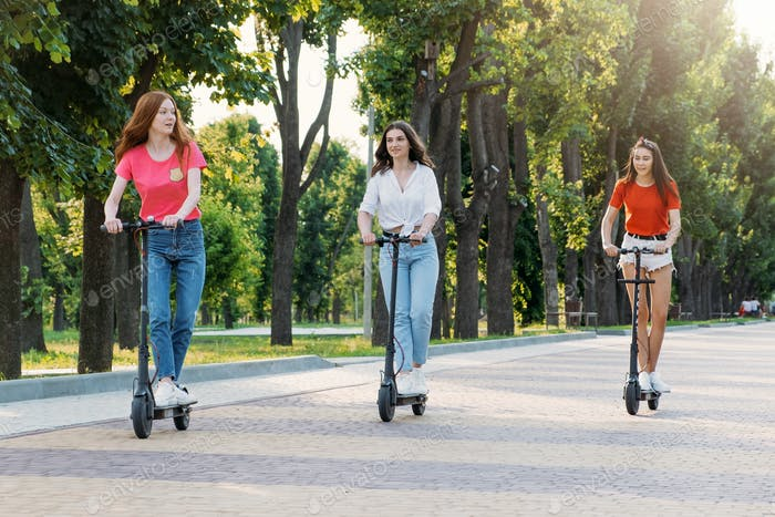 Three young girl friends on the electro scooters having fun in city street at summer sunny day