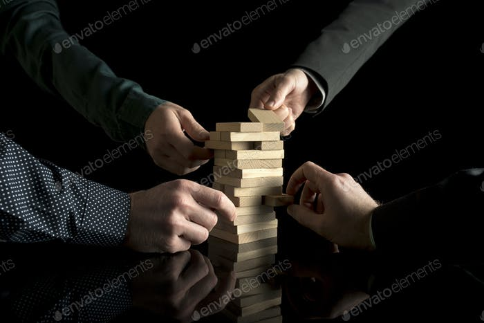 View of four male hands pulling pieces from tower
