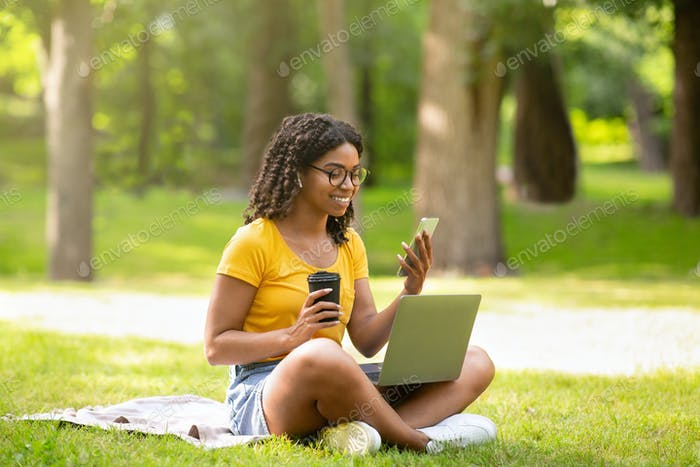 Cool black girl with coffee, smartphone and laptop computer studying online at summer park