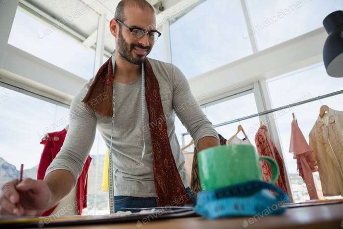 Low angle view of smiling designer working at table