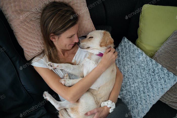 Young woman cuddling with her cute white dog sleeping in her lap