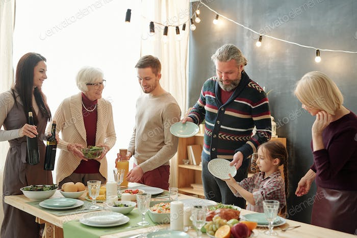 Family of five taking plates for snacks and preparing drinks before celebration