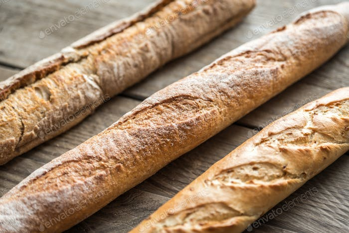 Three baguettes on the wooden background