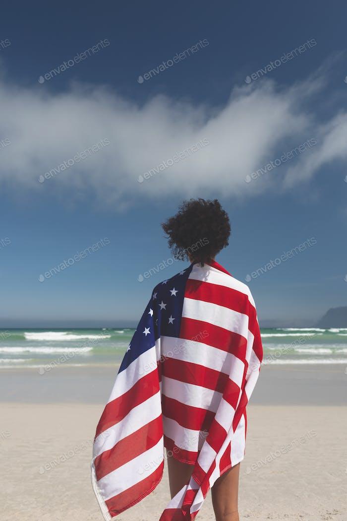 Rückansicht der schönen Mixed-Race Frau in amerikanischer Flagge am Strand an einem sonnigen Tag eingewickelt