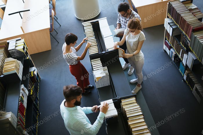 Happy young university students studying with books in library