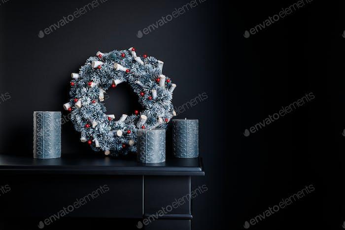 Graue Kerzen und Weihnachtskranz auf einem dekorativen Kamin gegen schwarze Wand