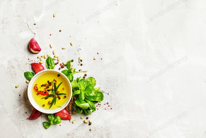 Food background, olive oil, cedar nuts, spices and herbs, green basil and garlic