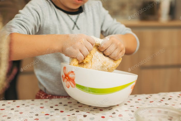 Close-up child hands making dough for biscuits