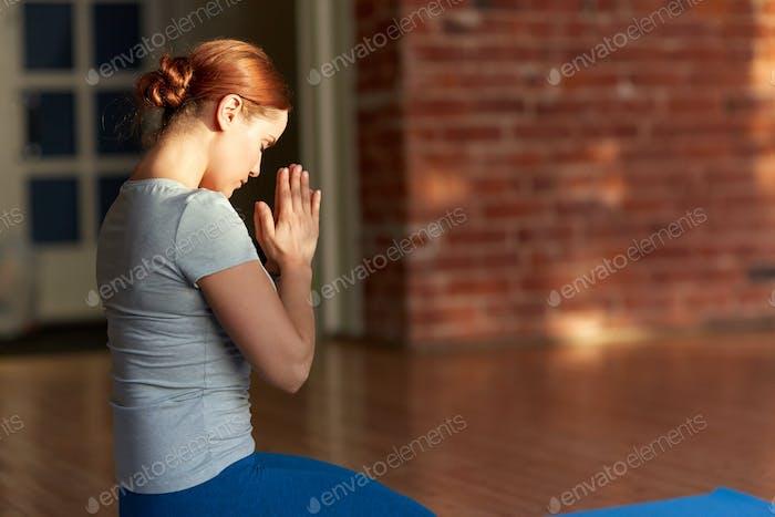 Frau meditiert im Yoga-Studio