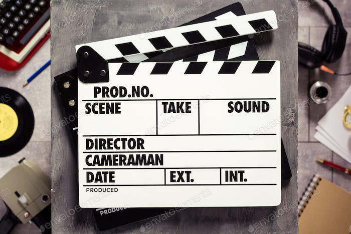 Movie clapboard or  clapper at old table. Clapperboard and screenwriter or composer  concept