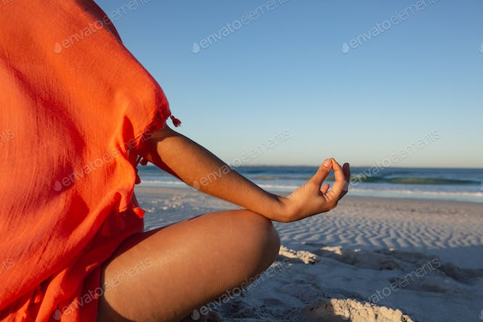Mid section of mixed race woman doing yoga on beach in the sunshine