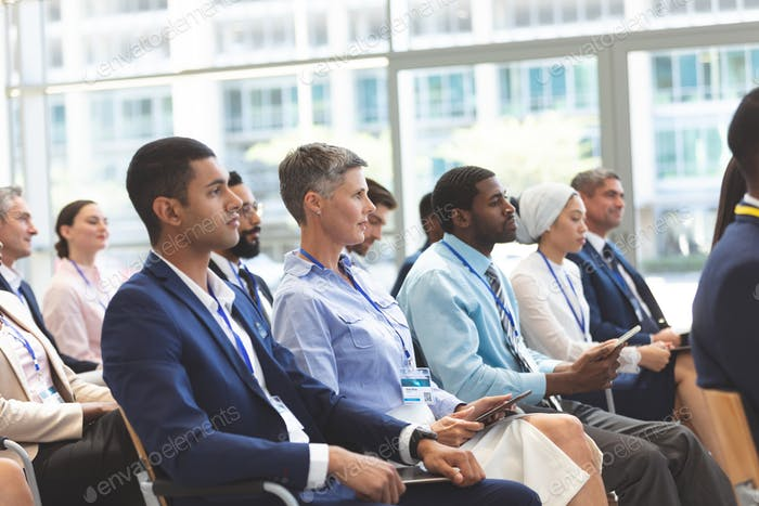 Side view of diverse business people with tablets attending a business seminar in office building