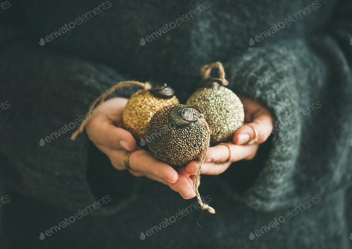 Woman in sweater holding golden and silver balls in hands