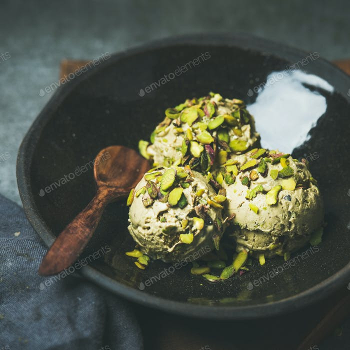 Homemade pistachio ice cream scoops with crashed nuts, square crop
