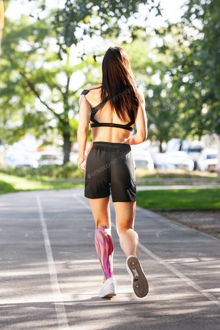 Woman with kinesiological taping running at stadium