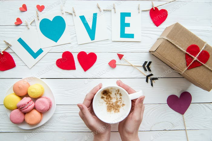 Top view of human hands holding cup of cappuccino with macaroon cookies, romantic decoration on