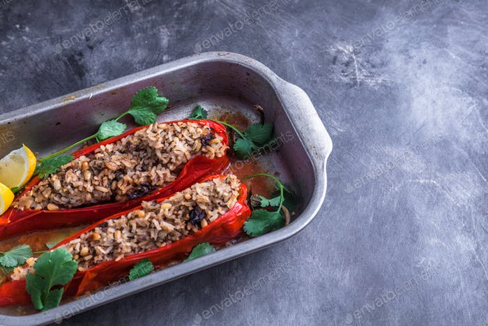 Stuffed peppers in iron cooking pot on dark rustic kitchen table background, top view, copyspace