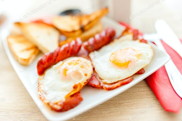 close-up of healthy breakfast with fried eggs, bacon, sausages,