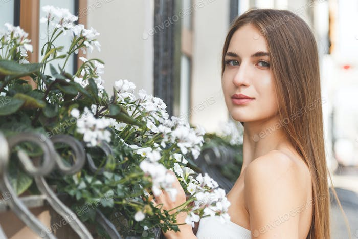 Sensual calm portrait of beautiful young woman in blooming bush with white flowers of petunias.