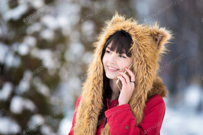 Young woman on mobile phone outdoors in wintertime